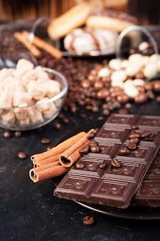 Schokoladentafeln neben zimtschnecken und anderen süßigkeiten und bonbons auf holzuntergrund