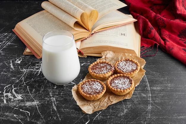Schokoladentartaletten mit gehackter kokosnuss und milch.