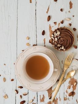 Schokoladentörtchen dienten mandelnüsse mit tasse tee und goldenem tischbesteck auf schäbigem weißem hölzernem hintergrund
