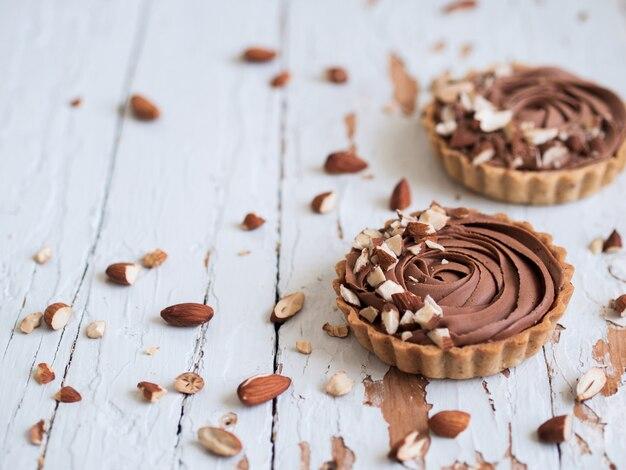 Schokoladentörtchen dienten mit mandelnüssen auf schäbiger weißer holzoberfläche