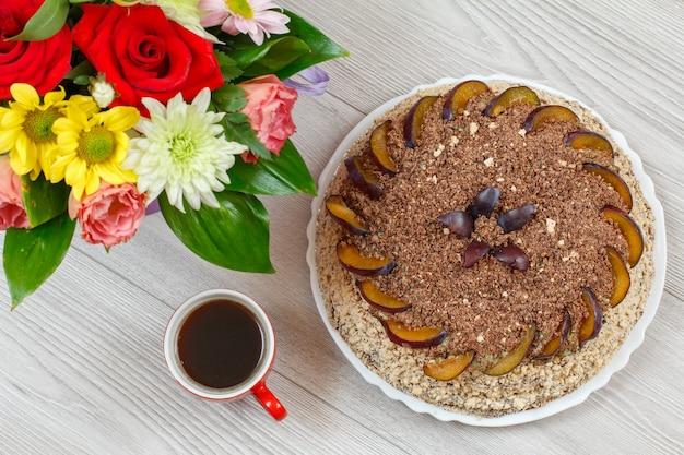 Schokoladentorte dekoriert mit pflaumen, einem blumenstrauß und einer tasse kaffee auf den grauen holzbrettern