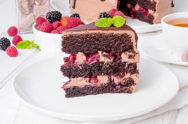 Schokoladentorte mit kirschfüllung und frischen beeren auf die oberseite auf einer weißen platte.