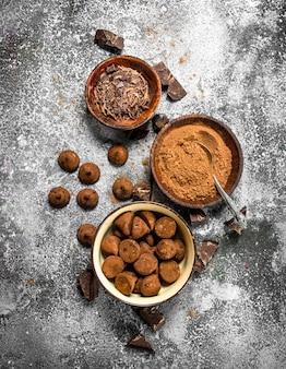 Schokoladentrüffel, kakaopulver und geriebene schokolade in schalen. auf einem rustikalen tisch.