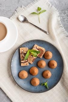 Schokoladentrüffel mit stück milchschokolade auf blauer keramischer platte auf grauem konkretem hintergrund.