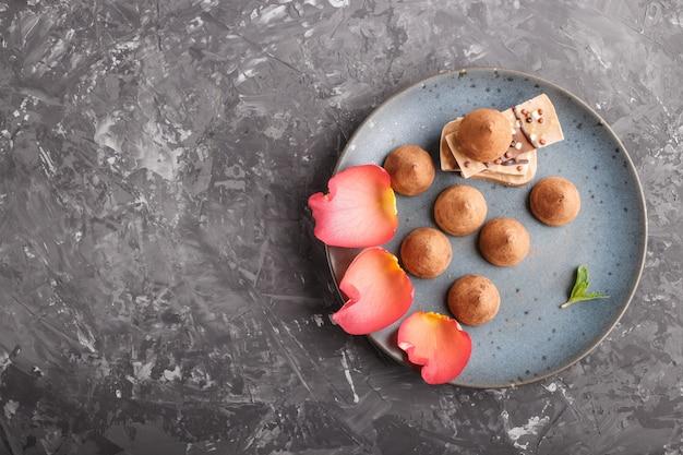 Schokoladentrüffel mit stück milchschokolade auf blauer keramischer platte auf schwarzem konkretem hintergrund.