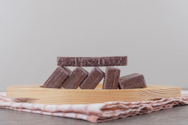 Schokoladenüberzogene waffeln auf einer holzplatte auf marmor