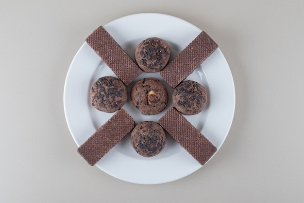 Schokoladenüberzogene waffeln und schokoladenkekse auf einer platte auf marmorhintergrund.
