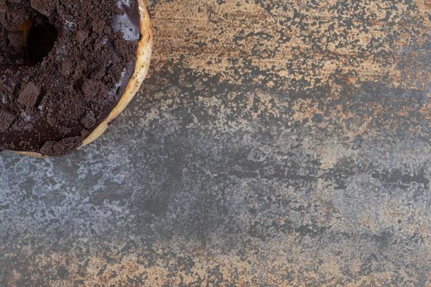 Schokoladenüberzogener donut auf marmoroberfläche