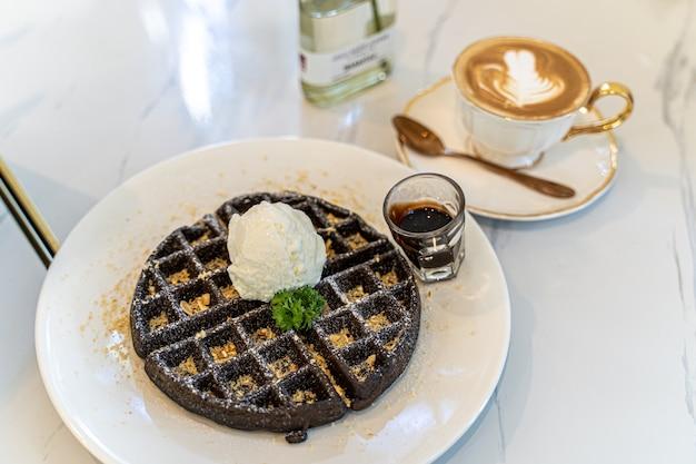 Schokoladenwaffel mit vanilleeis wird mit heißem kaffee serviert