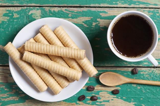 Schokoladenwaffel rollt im teller und in der tasse kaffee auf der draufsicht des alten grünen hölzernen hintergrundes