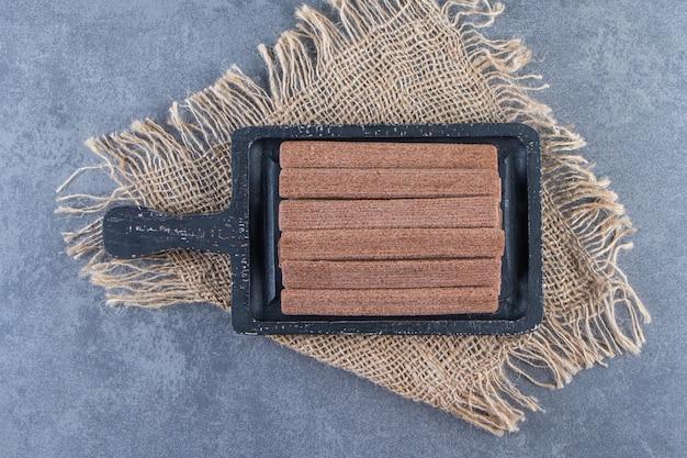Schokoladenwaffel rollt in einem brett auf einer textur auf der marmoroberfläche