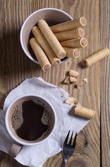 Schokoladenwaffel rollt in einer schüssel und tasse kaffee auf einem holztisch, ansicht von oben