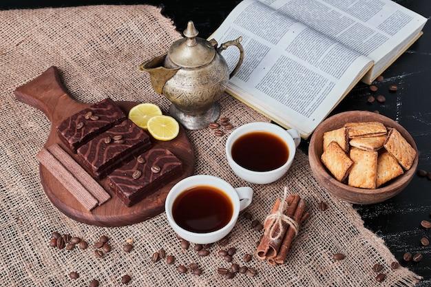 Schokoladenwaffeln mit einer tasse tee und keksen.