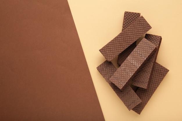 Schokoladenwaffeln mit kaffee auf beige und braun