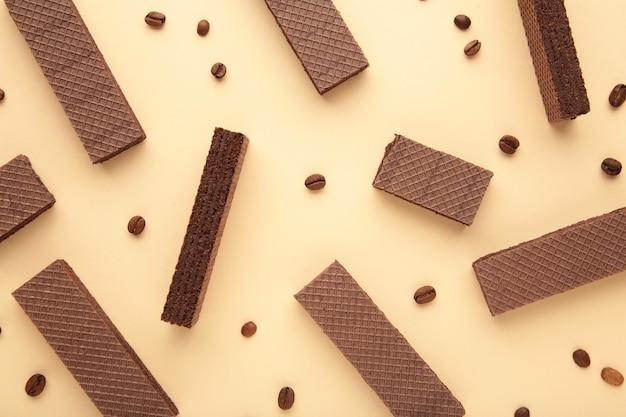 Schokoladenwaffeln mit kaffee auf beigem hintergrund. draufsicht