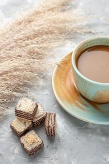 Schokoladenwaffeln mit milchkaffee auf grauweiß