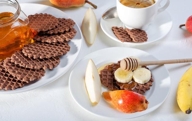 Schokoladenwaffeln mit roter birne, honig und banane zum frühstück auf weißem hintergrund.
