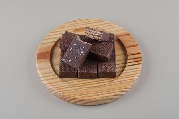 Schokoladenwaffeln zusammengebündelt auf einer hölzernen platte auf marmorhintergrund.