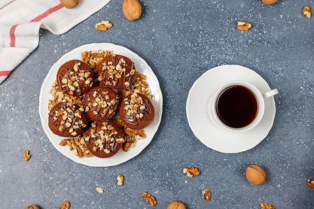 Schokoladenwalnussmuffins mit kaffeetasse mit walnüssen auf dunkler oberfläche