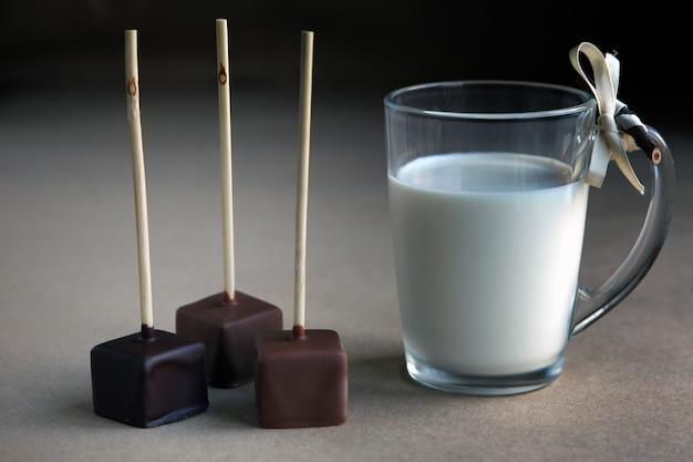 Schokoladenwürfel am stiel mit milchbecher und aromatischem kakao und schokolade auf braunem hintergrund, nahaufnahme. heißer kakao mit milch im transparenten glasbecher, gebrochene schokoladenwürfel haselnuss