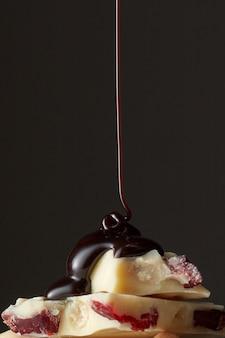 Schokoladenzyrop, der auf ein stück weiße schokolade gießt