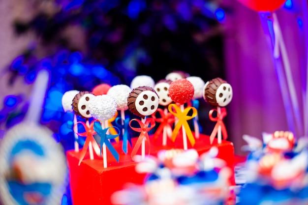 Schokoriegel auf der geburtstagsfeier des jungen mit vielen verschiedenen süßigkeiten, popcorn, getränken und großem kuchen