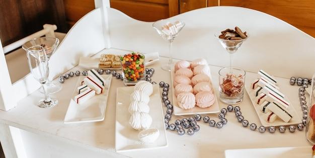 Schokoriegel beim bankett. hochzeitstisch mit süßigkeiten, kuchen, gebäck, muffins, zuckerleckereien. veranstaltung im restaurant