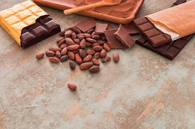 Schokoriegel, kakaobohnen und puder auf schmutzhintergrund
