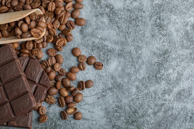Schokoriegel mit kaffeebohnen auf grau.