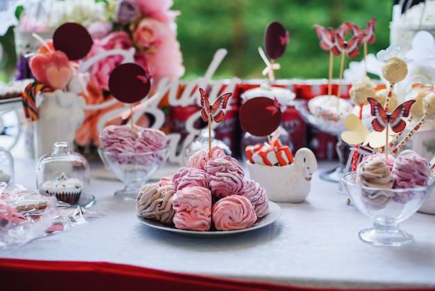 Schokoriegel mit marshmallows und cupcakes, dekoriert mit blumen und schmetterlingen