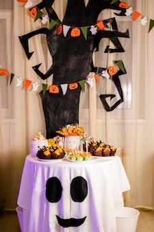 Schokoriegel mit süßigkeiten zur feier von halloween. riesiger schwarzer baum mit dekorationen auf dem hintergrund