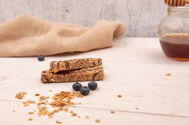Schokoriegel-müsli mit honig auf einem hölzernen hintergrund.