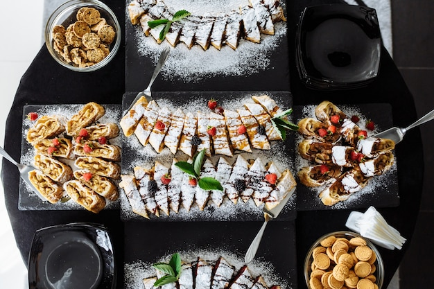 Schokoriegel. tisch mit verschiedenen süßigkeiten für die party. desserttisch für hochzeitsfeier. lecker dekoriert. süßigkeiten, bonbons, desserts, cupcakes, törtchen, makronen, kuchen und muffins.