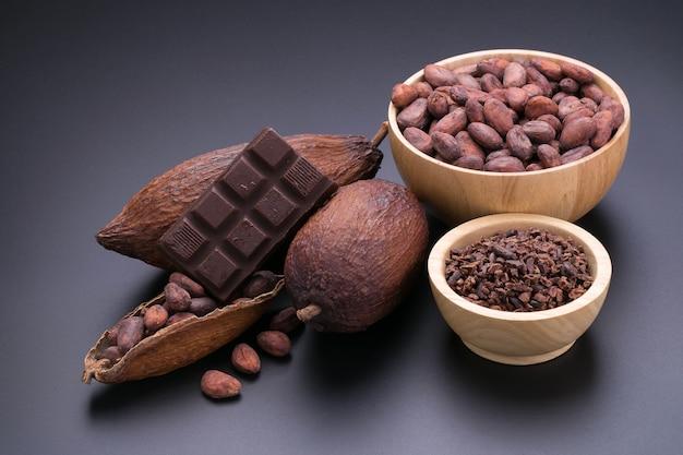Schokoriegel und getrocknete kakaohülse auf schwarzem hintergrund