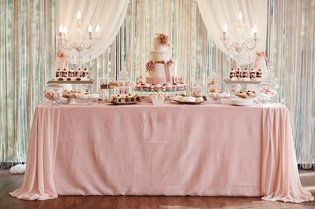 Schokoriegel und hochzeitstorte. tabelle mit bonbons, buffet mit kleinen kuchen, süßigkeiten, nachtisch.