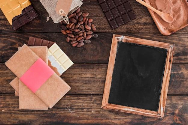 Schokoriegelstapel, leerer hölzerner schiefer, kakaobohnen und puder auf tabelle