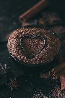 Schokoriegelstücke mit kakaopulver und herzform im dunkeln