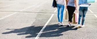 Schöne asiatische Mädchen, die Einkaufstaschen bei draußen stehen halten