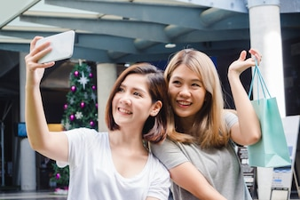 Schöne asiatische Mädchen, die Einkaufstaschen, unter Verwendung eines intelligenten Telefons selfie und eines Lächelns halten