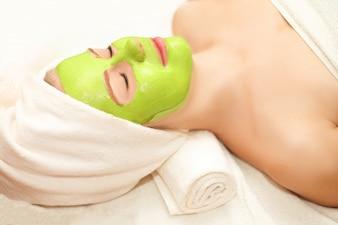 Schöne glückliche Frau im Badekurort, der Gesichtsmaskenbehandlung macht