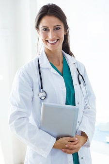 Schöne junge Ärztin, die Kamera im Büro betrachtet.