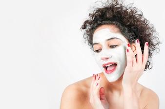 Schöne junge Frau, die Gesichtsmaske auf ihrem Gesicht getrennt über weißem Hintergrund anwendet