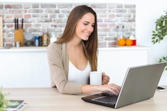Schöne junge Frau, die ihren Laptop in der Küche verwendet.