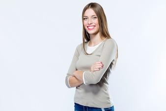 Schöne junge Frau, die Kamera über weißem Hintergrund betrachtet.