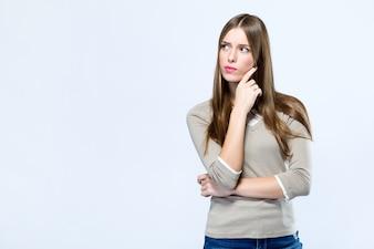 Schöne junge Frau, die über weißem Hintergrund denkt.
