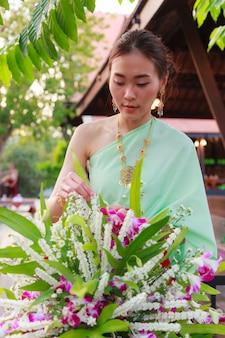 Schöne thailändische Asiatin im traditionellen thailändischen Kostüm der Weinlese Blumenvase vereinbarend.