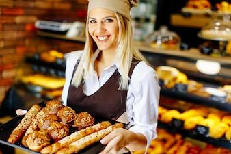Schöne weibliche Bäckerei, die mit verschiedenen Arten des Gebäcks und des Brotes im Bäckergeschäft aufwirft