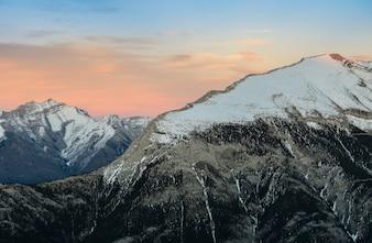 Schöner Schnee bedeckte Berge gegen den Dämmerungshimmel an Nationalpark Banff in Alberta, Kanada mit einer Kappe.