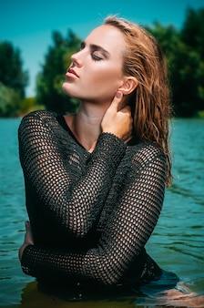 Schönes Brunettemädchen in der guten Form in Mode, die Suite schwimmt