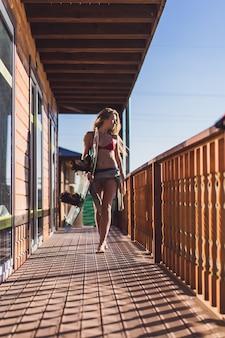 Schönes Mädchen mit langen Haaren mit einem Wakeboard